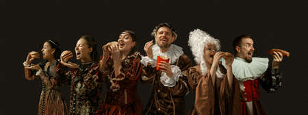 Favorite fast food tastes. Medieval people as a royalty persons in vintage clothing on dark background. Concept of comparison of eras, modernity and renaissance, baroque style. Creative collage.
