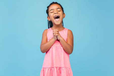 Singing. Happy longhair brunette little girl on blue studio background with copyspace for ad. Looks happy, cheerful, sincere. Childhood, education, human emotions, facial expression concept.