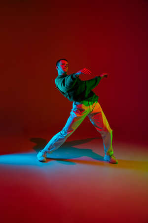 Freedom. Stylish sportive boy dancing hip-hop in stylish clothes on colorful background at dance hall in neon light. Youth culture, movement, style and fashion, action. Fashionable bright portrait.