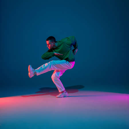 Inspired. Stylish sportive boy dancing hip-hop in stylish clothes on colorful background at dance hall in neon light. Youth culture, movement, style and fashion, action. Fashionable bright portrait.