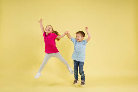 Jumping, dancing. Childhood and dream about big and famous future. Pretty little kids isolated on yellow studio background. Dreams, imagination, education, facial expression, emotions concept. Imagens
