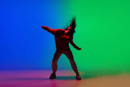 Modern. Stylish sportive girl dancing hip-hop in stylish clothes on colorful background at dance hall in neon light. Youth culture, movement, style and fashion, action. Fashionable bright portrait. Фото со стока