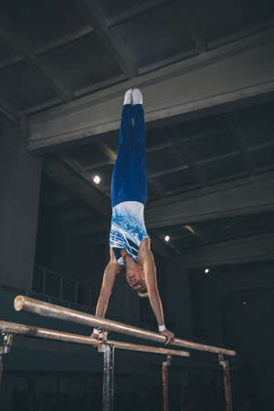 Energy. Little male gymnast training in gym, composed and active. Caucasian fit boy, athlete in sportswear practicing in exercises for strength, balance. Movement, action, motion, dynamic concept