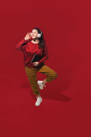 Dancing with headphones. High angle view of young woman on red studio background. Human emotions and facial expressions concept. Full length portait, copyspace for ad. Fashion, retro style.