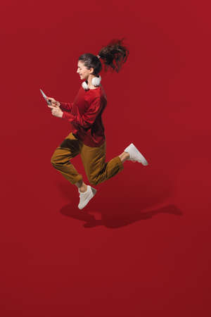 Dancing with headphones and tablet. High angle view of young woman on red studio background. Human emotions and facial expressions concept. Full length portait, copyspace for ad. Fashion, retro style. Stockfoto