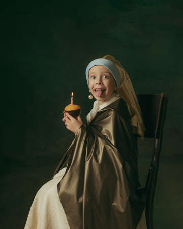 Birthday cake. Medieval little girl as lady with a pearl earring on dark studio background. Concept of comparison of eras, childhood, ancient. Stylish, creative, art vision, new look of artwork.