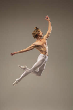Muscular. Young and graceful ballet dancer isolated on studio background in flight, jump. Art, motion, action, flexibility, inspiration concept. Flexible caucasian ballet dancer, moves in glow.