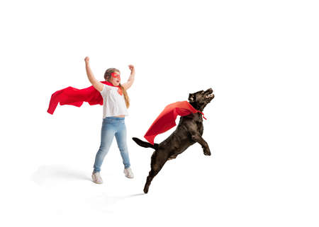 Child pretending to be a superhero with her super dog isolated on white studio background
