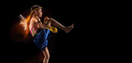 Little boy exercising thai boxing on black background. Fighter practicing, training in martial arts in action, motion. Evolution of movement, catching moment.