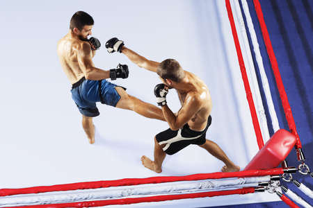 Two professional fighters punching or boxing isolated in the fight ring. High angle view. Collage