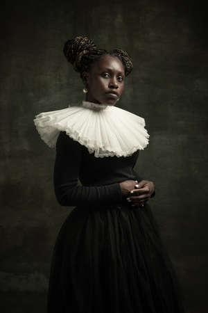 Portrait of medieval African young woman in black vintage dress with big white collar posing isolated on dark green background. Standard-Bild