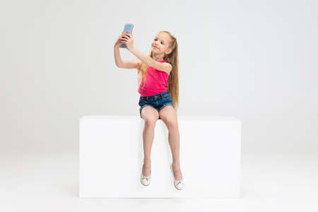 One beautiful little girl in casual clothes sitting on box isolated on white studio background. Happy childhood concept.
