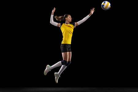 Female professional volleyball player with ball isolated on black studio background. The athlete, exercise, action, sport, healthy lifestyle, training, fitness concept.