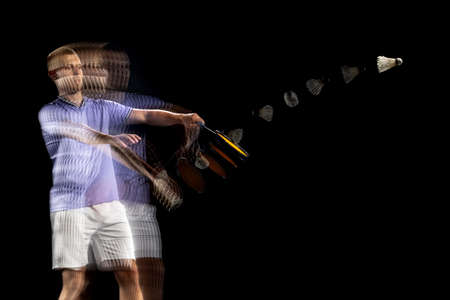 Spectacular trajectory of movement. One young male badminton player, shuttler training isolated on dark background. Stroboscope effect. Foto de archivo