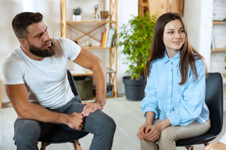 Two young people, married couple sitting in psychologists office. Look interested, calm, happy