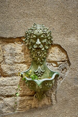 Roman Fountain With Green Plant On A Stone Wall at Barjac Gard Occitanie France
