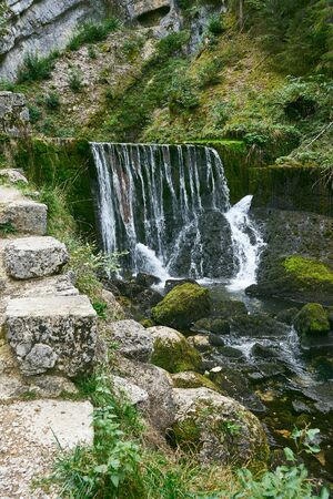 Waterfall at Source du Doubs Mouthe Franche Comté France with Green Plants On A Sunny Day Stock Photo