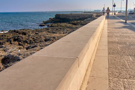 Young Blonde Kid Walking On A Parapet Along The Sea And Holding His Mother Hand On A Sunny Day On The Coast Of The Puglia Region in Italy Banco de Imagens
