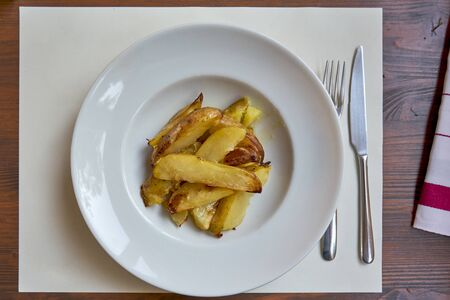 Roasted Potatoes Served On A Withe Plate On A Wooden Table.