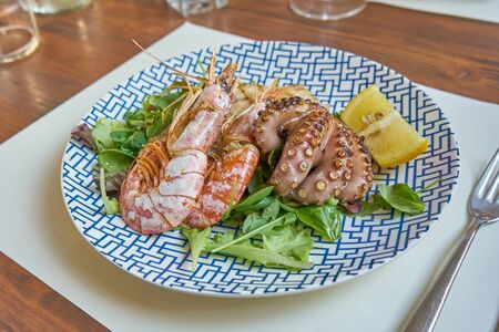 MIxed Grilled Seefood Including Schrimps Tuna Steak And Octopus And Salad Served On A Modern Dressed Table Banco de Imagens
