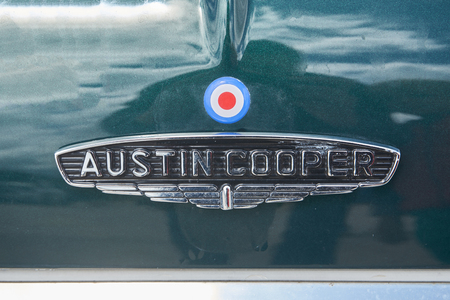 Pontarlier - Bourgogne Franche Comté France - June 16th 2019 - The Sun Shines Over A Austin Cooper Logo Sitting On A Green Austin Mini Car That Parks At A Local Car Rallye. Редакционное