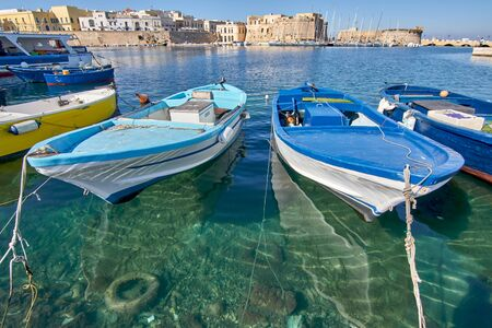 Typical Southern Italy Fishing Boats At Gallipoli Harbour Sit In Front Of Medieval Castle During a Sunny And Hot Autumn Day