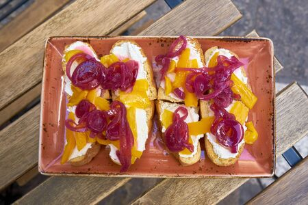 Ricotta With Toasted Beard With Candied Peppers And Red Onion Slices Фото со стока