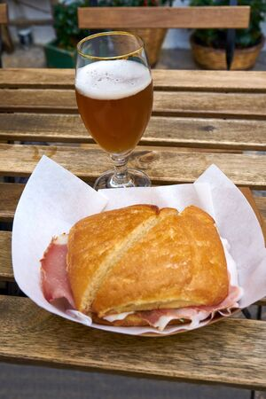 Italian dry ham sandwich on wooden table with glass of beer