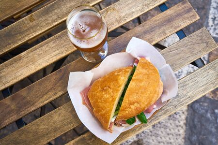 Italian dry ham sandwich with lambs lettuce salad on wooden table with glass of beer