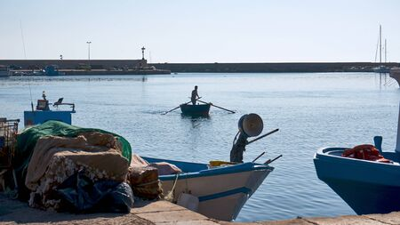 Italian Fisherman Rowing On His Traditional Apulian Boat In The Middle Of Gallipoli Harbour Фото со стока