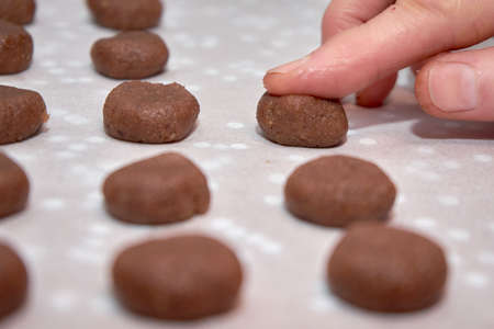 Woman's Hand Shaping A Ball Of Chocolate Dough Intended To Become A Christmas Cookie