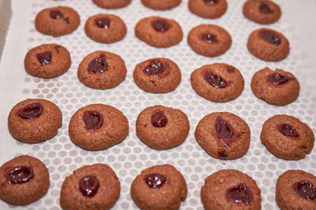 Chocolate Dough And Cherry Jam On A Sheet Of Baking Paper Intended To Be Baked To Become Cookies