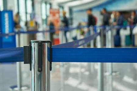 Attachment of the retractable belt. Portable tape barrier. Fence strip Blue Color. Airport Scene With Passengers Waiting For Boarding