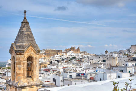 View of the old white town of Ostuni and the cathedral at sunrise. Brindisi, Apulia in southern Italy. Europe.