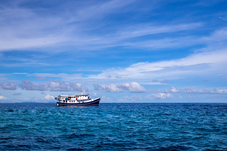 Thai fishing boat on the andaman ocean sea with blue sky