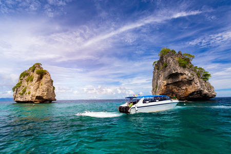 net: Thai travel speed boat with anchorman  in andaman ocean sea with large rock mountain with blue sky