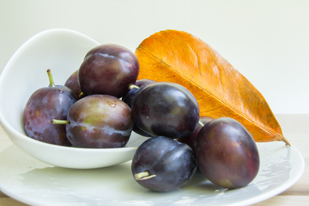 Plums spilling from a white bowl with a painted leaf.