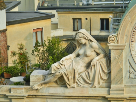 partially nude: Marble sculpture of a partially nude woman reclining. Detail of one side of a clock on top of a building across from the Duomo, Milan, Italy. Stock Photo