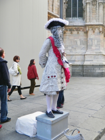period costume: Milan, Italy, October 15, 2010- An unidentifed street performer attracts attention as a human statue, dressed in 18th century period costume in Piazza del Duomo just steps away from Duomo di Milano and Galleria Vittorio Emanuele II. The fashion capital