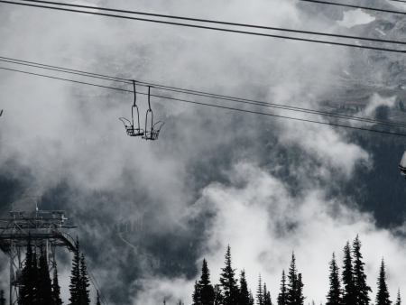 Two empty ski lifts cross paths in fast moving clouds high above the alpine forest, Whistler, Canada photo