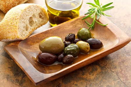 olive green: Olives on wooden plate with bread and rosemary Stock Photo