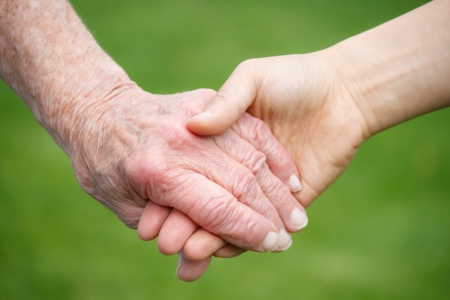 aging: Senior and Young Women Holding Hands