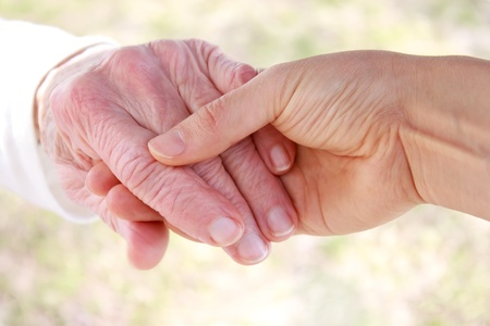 touching hands: Young hand holding seniors hand Stock Photo