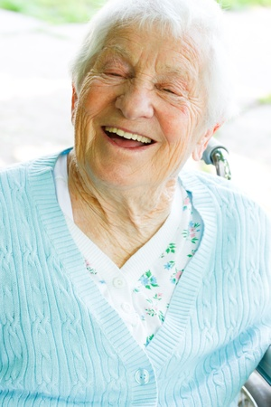Happy senior lady in wheelchair in spring day