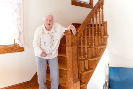 Senior woman standing in front of stairs photo