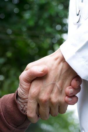 Doctor helping senior lady, holding her hand Foto de archivo