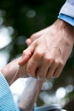 Helping senior woman, holding her hands photo