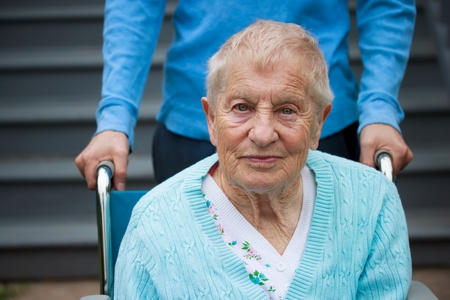 caretaker: Old women in wheelchair with caretaker Stock Photo
