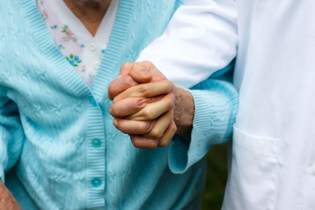 male senior adult: Senior lady with doctor, holding hands Stock Photo