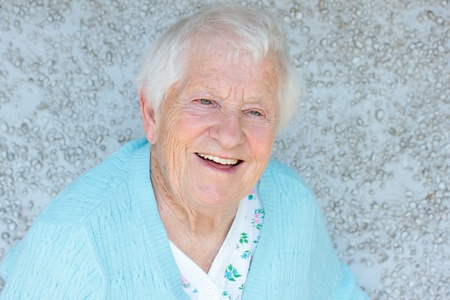 aging woman: Happy senior lady smiling in front of light blue stone wall